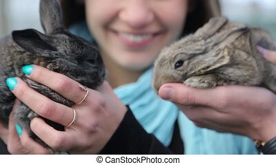 Men and girl holding rabbits in hands