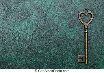 vintage key heart shape on a green leather background