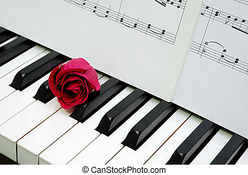 Red rose and music score on piano keyboard