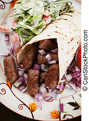 Cevapcici, bosnian minced meat kebab with onion, wrapped in...