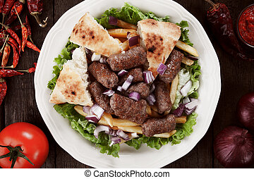 Cevapcici, bosnian minced meat kebab served with french...