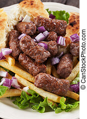 Cevapcici, bosnian minced meat kebab with onion and french...
