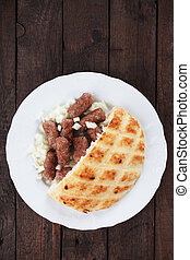 Cevapcici, bosnian minced meat kebab served with diced onion...