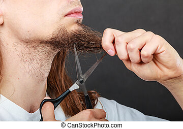 Man cutting his beard - Cut and shave concept Young man with...