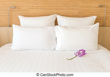 A white bed with 4 pillows and 2 head lights with a flower