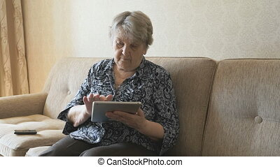 Elderly woman looks at pictures using a tablet