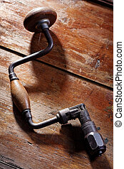 Old hand drill on wooden background