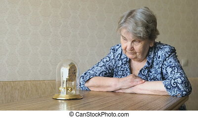 Old woman looks at the table clock with pendulum - Portrait...