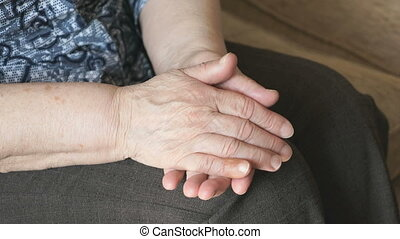 Woman strokes an old wrinkled woman's hand during a...