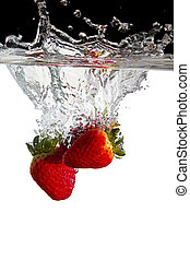 Some strawberries thrown in water with black and white...