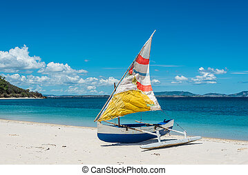 Malagasy outrigger pirogue with colorful makeshift sails on...