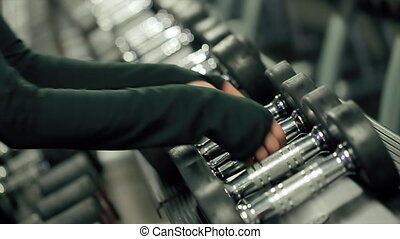 Hands of Female Athlete Taking Heavy Dumbbells