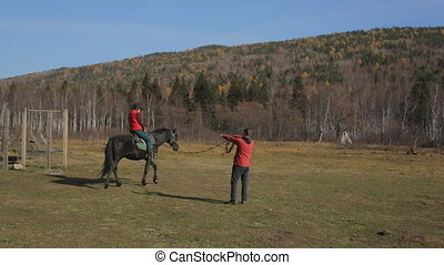 The equitation trainer is leading the horse in a circle with...