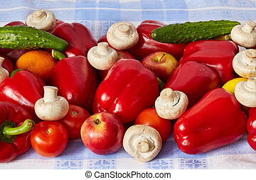 Many vegetable, fruits and mushrooms are on a towel