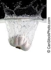 garlic thrown in water with black and white background