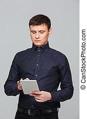 Businessman using tablet computer - Young businessman using...