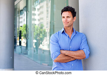 Business man standing outside with arms crossed - Portrait...