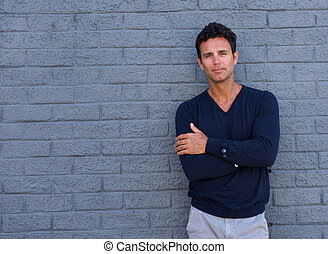 Mature man standing against gray wall with arms crossed -...