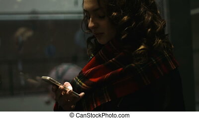 Adorable young lady chatting to her friends while going up in an elevator .