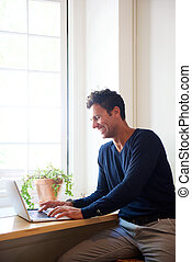 Smiling man using laptop at home - Portrait of a smiling man...