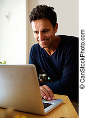 Middle aged man using laptop at home - Portrait of a middle...