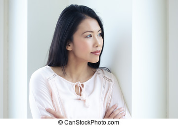 Asian Woman At Window - Pensive Asian woman standing at...