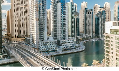 Dubai Marina at evening timelapse with trails of boats on...