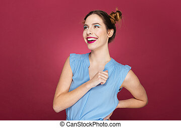 Smiling attractive young woman standing and laughing over...