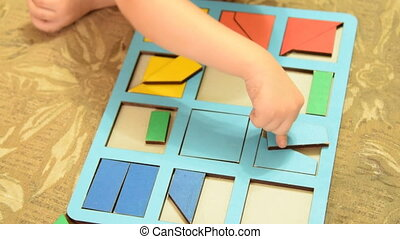 Child playing wooden logic game