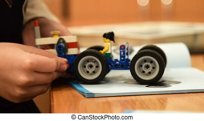 Child finishing robot toy - Close-up shot of a boy making...
