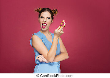 Funny angry young woman with candy cane standing and...
