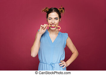 Lovely amusing young woman biting candy cane and winking