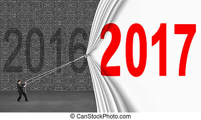 Businessman pulling down 2017 curtain covering old 2016...