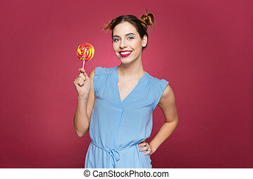 Smiling attractive young woman standing and holding colorful...