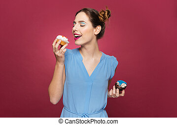 Happy young woman holding and eating cupcakes