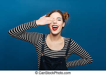 Cheerful cute young woman covered one eye by hand over blue...