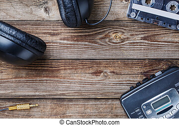 Cassette tapes, cassette player and headphones over wooden...
