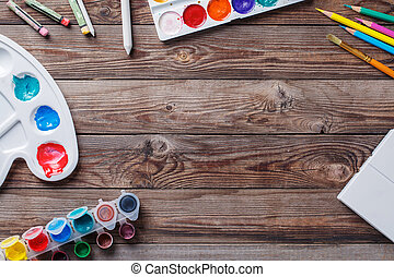 Paper, watercolors, paint brush and some art stuff on wooden...