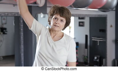 Senior woman stretching out in fitness room, mature, exercise, yoga
