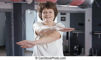 Senior woman doing exercises at gym, mature, fitness, stretching, yoga