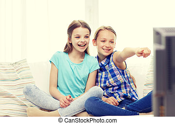two happy little girls watching tv at home - people,...