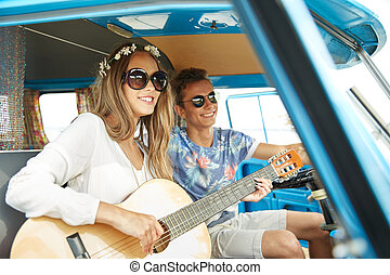 smiling hippie couple with guitar in minivan car - summer...