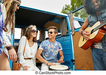 happy hippie friends playing music over minivan - summer...