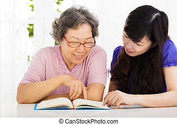 happy senior woman and  daughter  reading a book