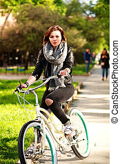 Young woman riding a bicycle in green city park
