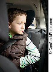 Offended little boy in car safety seat. Children car safety...