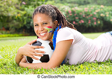 portrait of female soccer fan lying on the grass and smiling...