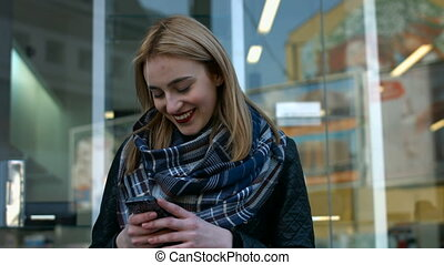 Pretty young blonde woman sending a message on her phone.