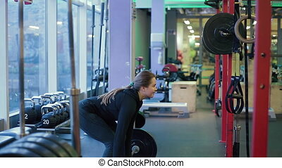 Young Woman Fails to Raise Heavy Dumbbell in Gym - Young...