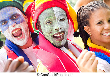 sports fanatics - three sports fanatics smiling with painted...